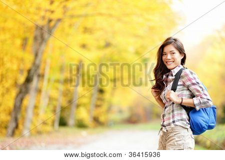 Fall hiking girl. Woman hiker portrait in forest in autumn colors. Beautiful young mixed race female on hike. Image from Mont Sutton, Quebec, Canada.