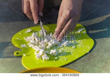 Female Hands Chopping Cheese With Knife On A Plastic Chopping Board