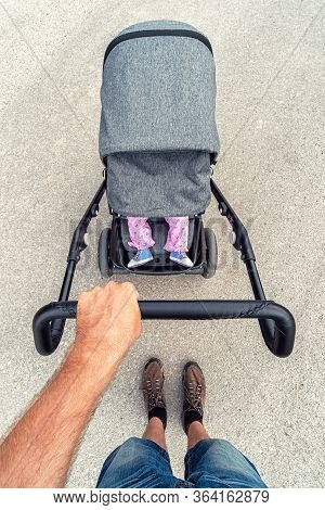 Legs Of Infant Girl Lying In Baby Stroller. Hand Of Father Pushing  A Pram
