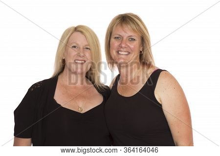Two Average Middle Aged Women Standing Together For A Portrait, On A White Background.