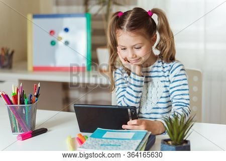 Distance Learning Online Education. Smiling Schoolgirl Girl With Digital Tablet At Home Studying Les