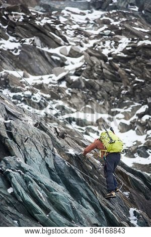 Back View Of Alpinist With Backpack Using Rope While Climbing Alpine Ridge. Man Climber Ascending Mo