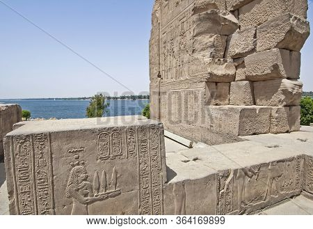 Hieroglypic Carvings On Wall At The Ancient Egyptian Temple Of Kom Ombo In Aswan With View Of Nile R