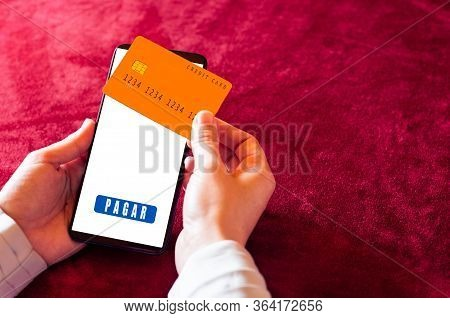 Human Hand Holding Smartphone With Online Shopping App And Credit Card. Pagar Is Pay In Spanish