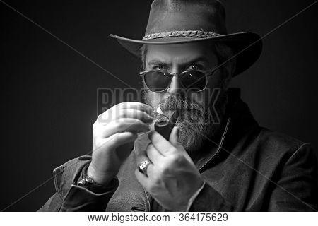 Menacing Vintage Cowboy Standing With Pipe For Smoking. Studio Shot Against Dark Background.