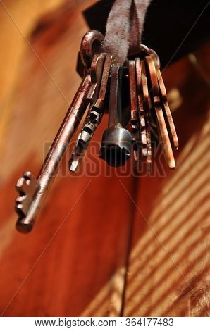 Bunch Of Keys In Hanging On Dirty Ribbon With Wooden Background. Vintage Keys Are Shining In Sunligh