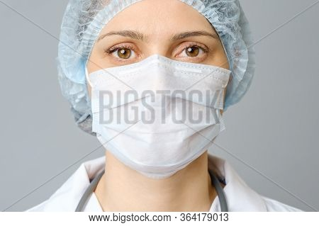 Portrait Of Young Female Doctor In Protective Medical Mask On Her Face And Cap On Her Head. Isolated
