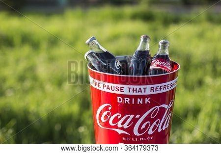 Atlanta Usa May 1 2020 Branded Coke Bucket Full Of Coca Cola Bottles Outdoors On Green Natural Backg