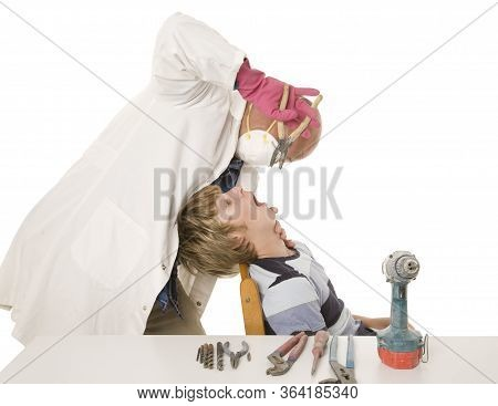 A Man Doing Do It Yourself Dentistry With Industrial Tools.