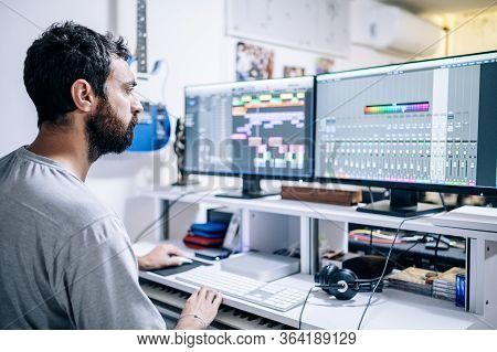 Musician Producer In Front Of Two Screens Working In Home Recording Studio.home Studio,music Concept
