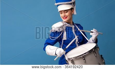 Drummer In A Blue Uniform Drums On A Drum, Show Program And Celebration. Funny Drummer Plays Drums A