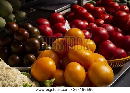 Colorful Vegetables On Counter Of Farmers Market. Variety Of Yellow, Red And Reddish Tomatoes In Tra