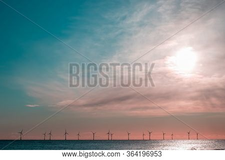 Sustainable Resource. Offshore Wind Farm Turbines On The Sea Horizon. Renewable Energy Background Im