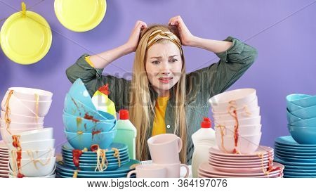 The Housewife In A Panic Holds Her Head In Her Hands And Looks At The Table With A Mountain Of Dirty