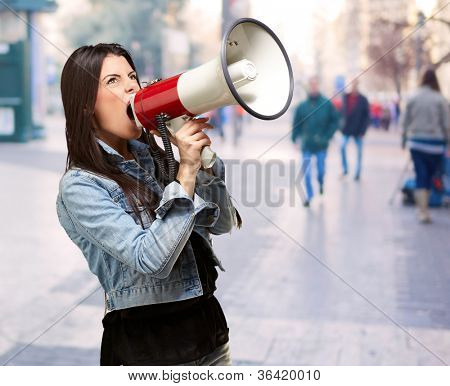 portrait of young woman screaming with megaphone at crowded street