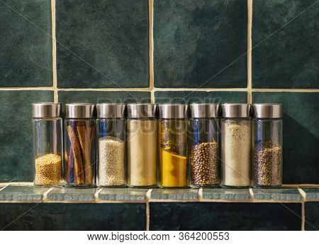 Spices In Glass Jars In The Kitchen. A Set Of Spices (turmeric, Coriander, Pepper, Cinnamon, Mustard