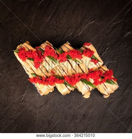 A Beautifully Decorated Serving Of Japanese Rolls. Tobiko Caviar, Chopped Green Onions. Shiny Surfac