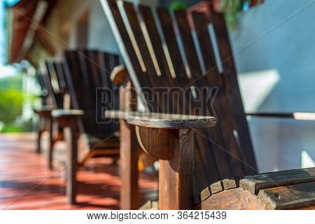 Empty Adirondack Arm Chairs In Row On Wood Deck , Focus On The Arm , Shallow Depth Of Field, Copy Sp