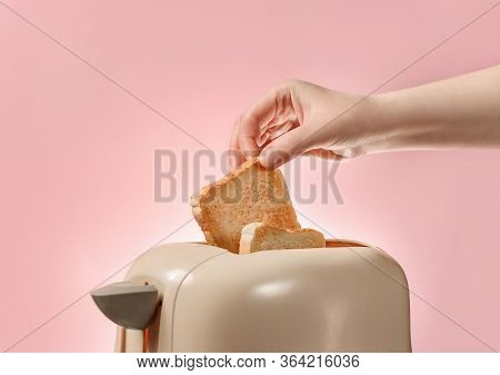A Female Hand Takes Out Toasted Bread Toast From A Toaster. Toaster With Ready-made Toasts And A Fem