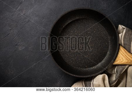Frying Pan Or Skillet With Stone Nonstick Coating On Black Slate Background. Top View With Copy Spac