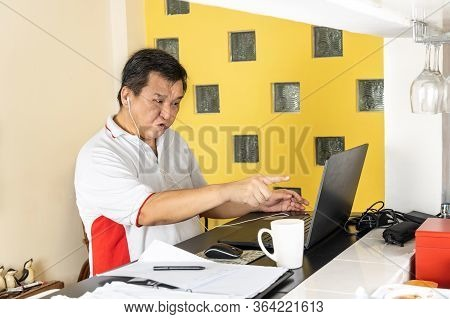 Matured Asian Business Man Pointing To Laptop In Stressful Expression In Work From Home Video Confer