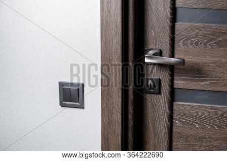 Two-key Switch Of Gray Color Near The Door, Plastic Mechanical Switch. The Light Switch Is Installed