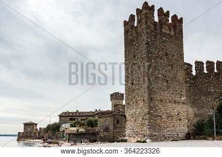 Sirmione, Italy, October 01, 2015 : Fragment Of The Fortress Wall With A Corner Tower And Promenade