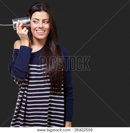 Female Holding A Metal Tin As A Telephone On A Black Background