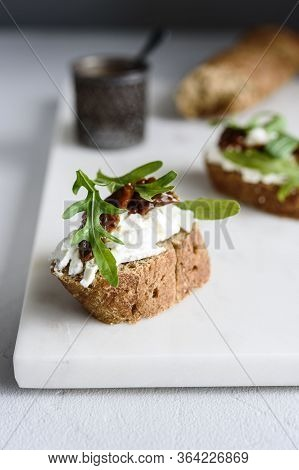 Italian Bruschetta (sandwich, Crostini, Toast) With Confit Tomatoes, Feta, Olive Oil And Arugula Lea