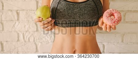 Closeup Sexy Young Woman Deciding To Choose Between Healthy Fruit Or Sweet Donut. Beautiful Slim Fit
