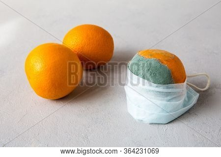 A Spoiled, Rotten, Inedible Orange Is Put On A Medical Mask That Protects Against Coronavirus During
