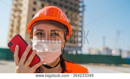 Female Construction Worker In Overalls And Medical Mask Flipping Through News About Coronavirus In M
