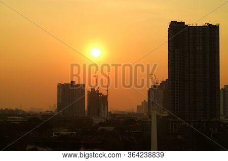 Dazzling Evening Sun On The Golden Sky Over The Silhouette Of City Construction Site
