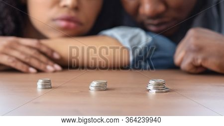 Poverty And Absence Of Money Concept. Stacks Of Coins Lying On Table In Front Of Sad African America