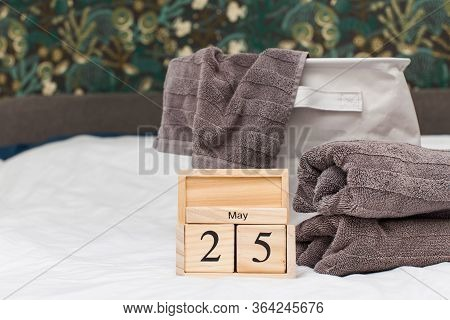 Gray Terry Towels On The Bed With White Linens And A Wooden Calendar Dated May 25. Towels Day. Copy
