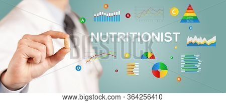 Nutritionist giving you a pill with NUTRITIONIST inscription, healthy lifestyle concept
