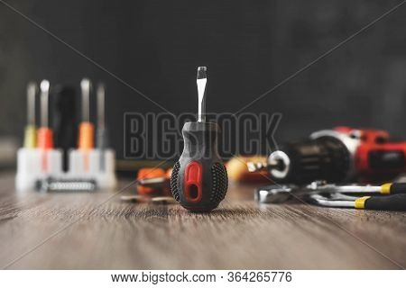 A Small Screwdriver Set Among The Tools On A Wooden Table