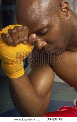 Close-up of an upset African American male boxer with head on wrapped hand