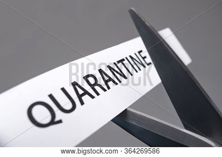 Scissors Cutting A Piece Of Paper With Quarantine Printed On It. Coronavirus Covid-19 Disease Pandem