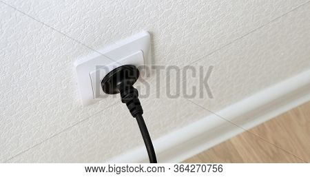 Hand Inserting Black Power Plug Into An White Electricity Socket. Close Up.