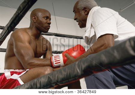 Senior coach advising boxer after the end of a round in the match