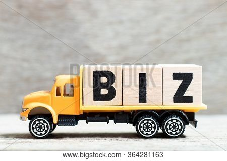 Truck Hold Letter Block In Word Biz (abbreviation Of Business) On Wood Background