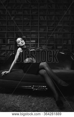 A Beautiful Brunette Girl, A Model In The Studio. Sun And Shadow. Standing In A Sexy Dress With A Re