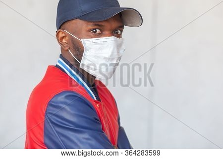Close Up Photo Of Handsome African Man In A Cap And Casual Clothes Wearing Medical Mask Shocked With