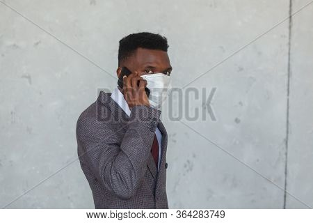 Covid, Covid-19, Coronavirus, Pandemic. Handsome African Black Man In A Suit Using Medical Mask As P