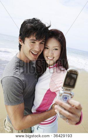 Couple taking self-portrait through cell phone on beach