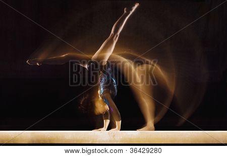 Female gymnast in motion on balance beam