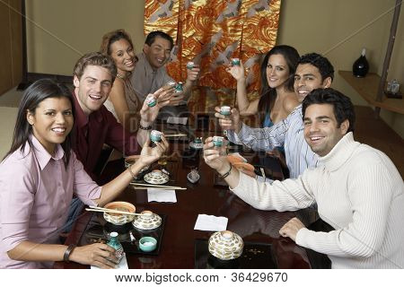 Group toasting Japanese saki cups in restaurant poster