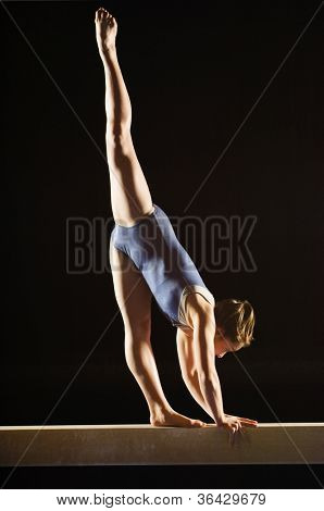 Female gymnast striking pose on balance beam