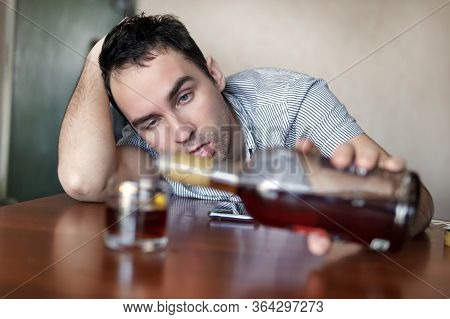 Sad Sad Young Alcoholic Sit At The Table With A Bottle Of Rum. The Face Of A Drunk Man. Stupid Emoti